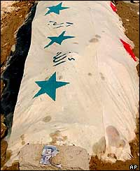 The grave of Saddam Hussein's younger son Qusay is marked with an Iraqi Dinar note showing Saddam's portrait, 2 August 2003