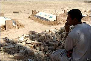 A family member grieves at the graves of Saddam Hussein's sons Uday and Qusay and Qusay's 14-year-old son Mustafa Hussein, 2 August 2003