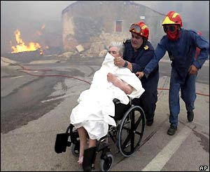 Woman in wheelchair shields her face from smoke as she is wheeled away from fire by firefighters