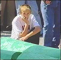 Boy next to coffins