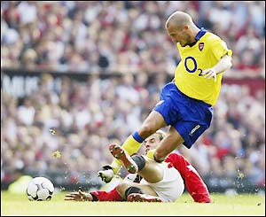 Man Utd's Phil Neville tries to stop Arsenal's Freddie Ljungberg pushing forward