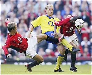 Fortune and Neville tackle Arsenal's Dennis Bergkamp