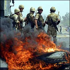 British soldiers stand by burning tires as clashes broke out between Iraqis and British troops