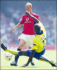 Arsenal's Sol Campbell launches a tackle on Man Utd's Nicky Butt