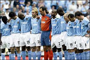 Manchester City players observe a minute's silence in memory of former City midfielder Marc-Vivien Foe