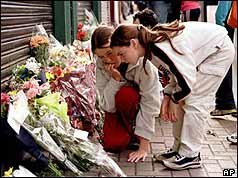 Girls read floral tributes to the victims