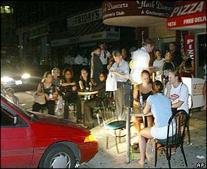 Patrons eat outside Leon's Pizza in Manhattan, under the lights of a parked car