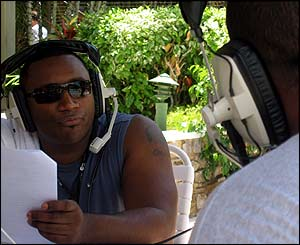 Rampage (background) talks to DJ Slic (foreground) poolside broadcast from Trinidad Carnival
