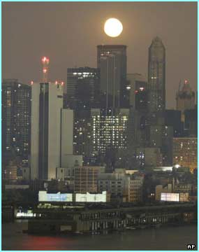 The moon's natural light shines over Manhattan hit by the biggest power failure in US history.