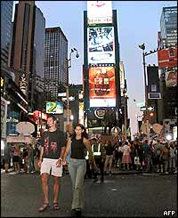 A couple walks across the street in Times Square in New York 15 August 2003 as power returned to the city