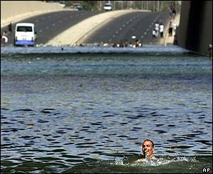 An Iraqi man cools himself in a flooded underpass