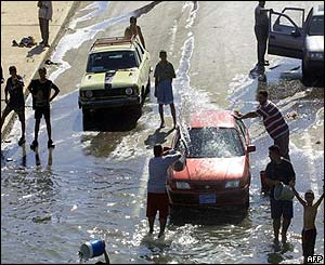 Iraqi people wash their cars with water flowing from a hole caused by the sabotage of a water pipeline in Baghdad