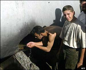 Iraqis drink from a hole in a water pipeline in Baghdad