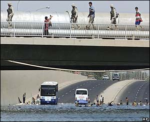 U.S. troops inspect a damaged water pipe as young Iraqis cool themselves in a flooded underpass
