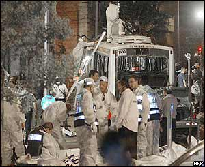 Police and paramedics search the scene of the blast