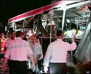 A crowd gathers around the wreckage of the bus
