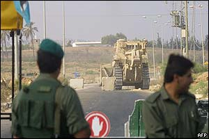 Palestinian security guards watch as an Israeli bulldozer sets up roadblocks
