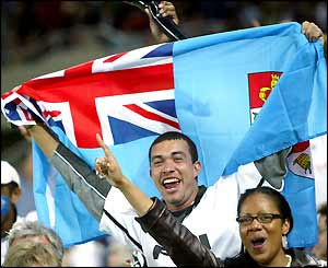 A fan waves the Fijian flag in the crowd