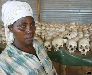 A Rwandan woman stands in front of genocide victim's remains
