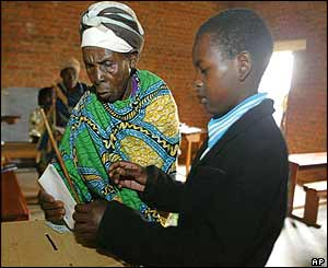 A boy helps an old lady to vote