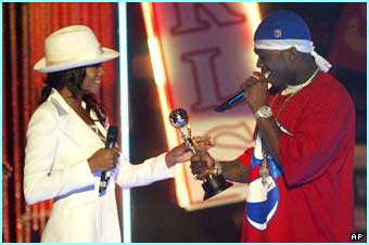 50-cent receives the award for the best artist of 2003,  from his girlfriend Vivicia A. Fox