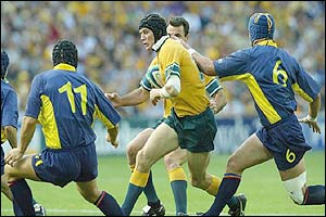 Australia's Stephen Larkham takes on the Romanian defence