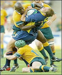 Romania Danut Dumbrava is tackled by two Australians