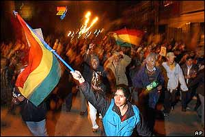 Woman waves huge Bolivian flag as protesters chant and raise their fists behind her