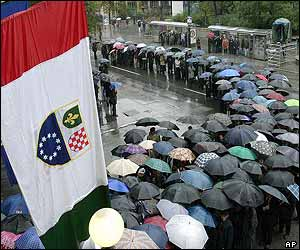 Flags hang in the foreground as people wait under umbrellas to pay their respects to former President Alija Izetbegovic