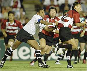 Yukio Motoki of Japan attempts to get away from the Fiji defence