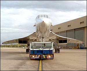 Concorde about to be towed from the BA engineering base at Heathrow, across a public road to Terminal 4 for her 1830 flight to New York, October 4 2003, by Stephen Daniels from Scotland