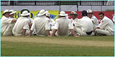 England's cricketers take a break while they wait for the floodlights to come back on in their match against Bangladesh