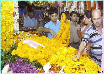 Hindus select garlands of marigolds at a flower stall in New Delhi