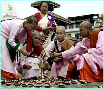 A group of Nepalese Buddhist nuns light lamps for Diwali in Kathmandu
