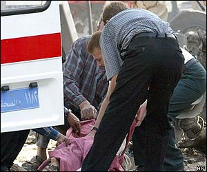 A body is carried out of the ICRC building by ambulance workers following the blast
