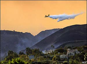 An air tanker drops water on a wildfire in Malibu.