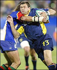 Romanian centre Valentin Maftei is tackled by Namibian flanker Schalk van der Merwe