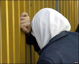 A woman bends her head on the fence of an Istanbul morgue