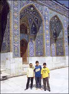 Three boys standing outside mosque in Kerbala, Iraq