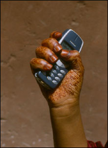 Henna-painted hand holding a cell phone