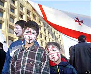 Children with faces painted in the colours of the Georgian opposition's flag