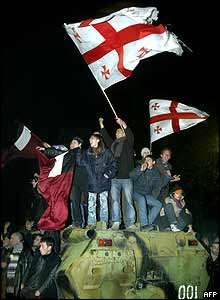 Jubilant Georgians mount an armoured vehicle near the president's residence