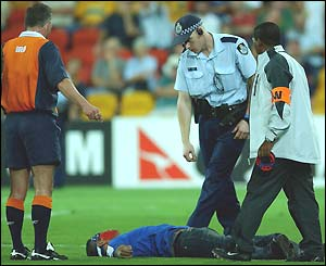 Police attend to a fan who ran onto the pitch