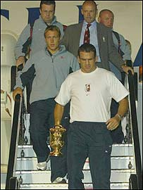 Jonny Wilkinson, Clive Woodward and Martin Johnson disembark at Heathrow