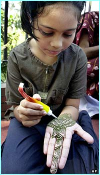 A Bangladeshi girl decorates her hand with henna, a popular form of fashion among women, especially during Eid