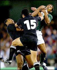 South Africa's Ashwin Willemse of takes the ball in front of Mils Muliaina of New Zealand