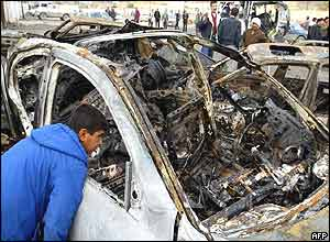 Iraqi youth looks into one of the vehicles destroyed in Samarra