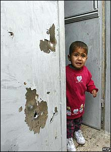 Child stands in a bullet-holed entrance in Samarra