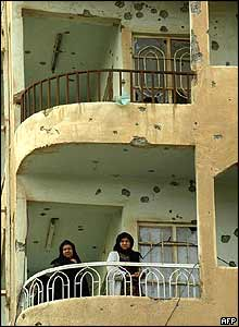 Two women stand on a bullet-riddled balcony