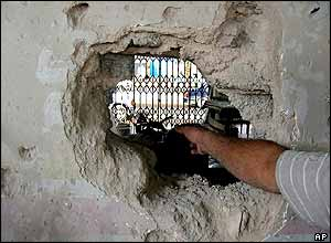 Iraqi points to hole in his shop wall caused by a missile